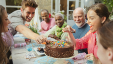 Family reaching for candy on chocolate birthday cake at patio table - CAIF09539