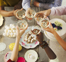 Overhead view friends toasting champagne glasses over Easter desserts - CAIF09545
