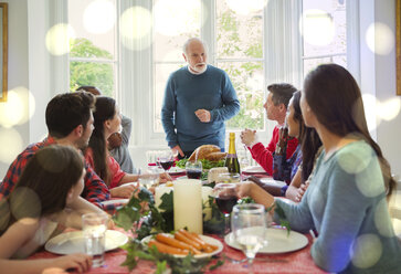 Grandfather preparing to carve Christmas turkey at dinner table - CAIF09557