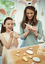 Mother and daughter wearing costume rabbit ears decorating Easter eggs - CAIF09563