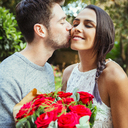 Affectionate man giving red rose bouquet to girlfriend, kissing her on cheek - CAIF09566