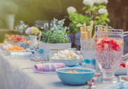 Strawberry water and desserts on garden party patio table - CAIF09575