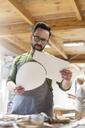 Artist examining pieces in studio - CAIF09617