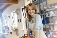Portrait smiling artist in studio - CAIF09626