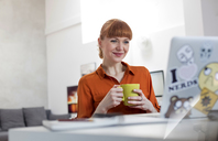 Smiling woman drinking coffee and working at laptop - CAIF09659