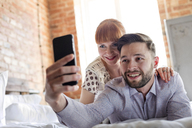 Couple laying on bed taking selfie with camera phone - CAIF09695