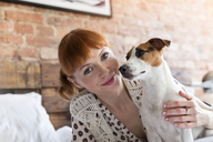 Portrait smiling woman with Jack Russell Terrier dog on bed - CAIF09698
