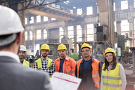 Steel workers listening to manager in meeting in factory - CAIF09782