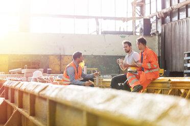 Steel workers enjoying lunch break in factory - CAIF09785