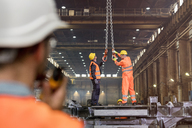 Steel workers adjusting crane hooks in factory - CAIF09800
