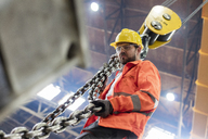 Steel worker holding crane chain in factory - CAIF09806