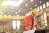 Engineer reviewing blueprints in steel factory - CAIF09815