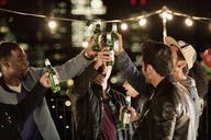 Young men toasting beer bottles at rooftop party - CAIF09821