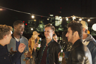 Young men drinking beer and talking at rooftop party - CAIF09830