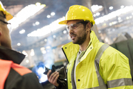 Steel workers talking in factory - CAIF09854