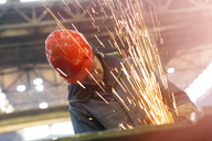Welder using welding torch with sparks in steel factory - CAIF09866
