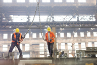 Steel workers with crane hooks in factory - CAIF09869