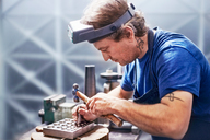Focused jeweler using hammer in workshop - CAIF09878