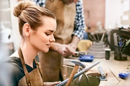 Female jeweler using equipment in workshop - CAIF09896