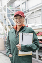 Portrait smiling worker with clipboard in food processing plant - CAIF09947