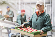 Portrait confident female worker carrying box of apples in food processing plant - CAIF09980