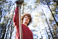 Low angle view of boy holding garden fork in forest - CAVF04864