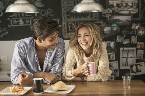 Happy couple sitting at breakfast table in home - CAVF04900