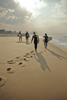Rear view of friends carrying surfboards while walking on sand at beach - CAVF04927