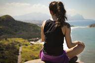 Rear view of woman relaxing on rock - CAVF04987