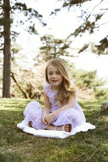 Portrait of happy girl sitting on blanket in backyard - CAVF05017