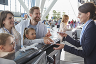Customer service representative helping family checking in with tickets at airport check-in counter - CAIF10015