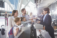 Customer service representative checking family tickets at airport check-in counter - CAIF10018