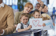 Mother and children with welcome signs for father at airport - CAIF10021