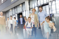 Family walking and running in airport concourse - CAIF10024