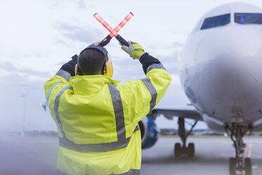 Air traffic controller guiding airplane with wand lights on tarmac - CAIF10030