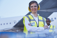 Portrait smiling female air traffic controller standing near airplane - CAIF10033