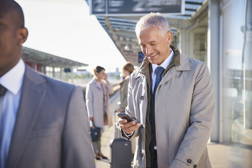 Businessman texting with cell phone outside airport - CAIF10036