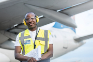 Air traffic controller with clipboard under airplane on airport tarmac - CAIF10039