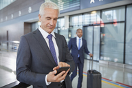 Businessman texting with cell phone in airport concourse - CAIF10045