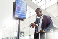 Businessman checking the time on wristwatch below arrival departure board at airport - CAIF10048
