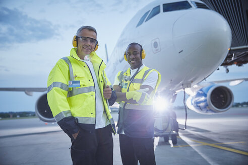 Portrait confident air traffic control ground crew workers near airplane on airport tarmac - CAIF10054