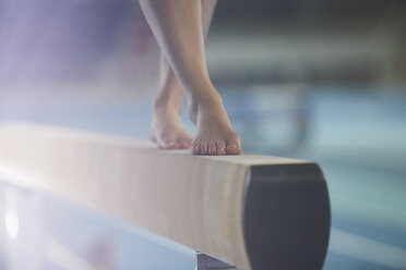 Bare feet of female gymnast performing on balance beam - CAIF10075