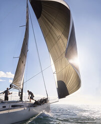 Wind pulling sail on sailboat on sunny ocean - CAIF10150
