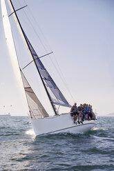 Friends sailing on heeling sailboat on ocean under blue sky - CAIF10168
