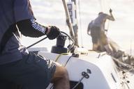 Man holding sailing rigging on sailboat - CAIF10177