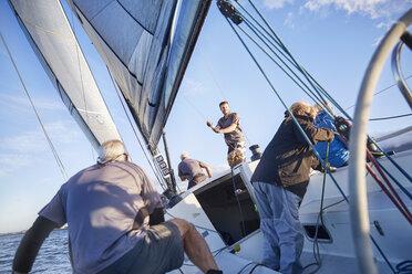 Men sailing adjusting rigging and sail on sailboat - CAIF10183