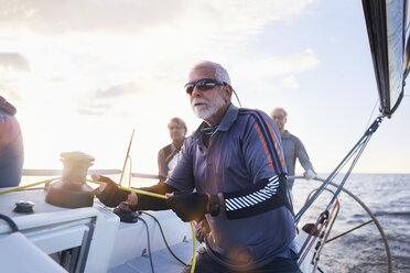 Retired man sailing holding rigging on sailboat - CAIF10189