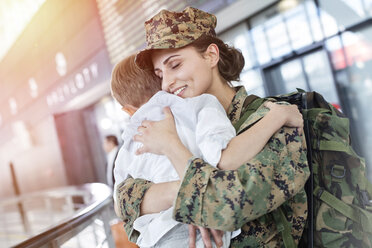 Son greeting and hugging soldier mom at airport - CAIF10195