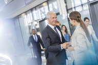 Business people greeting shaking hands in airport - CAIF10198