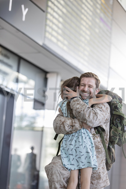Daughter greeting and hugging soldier father at airport - CAIF10201
